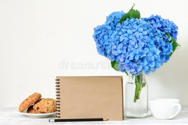 Kreatywnie egzamin próbny up z pięknym bukietem błękitni hortensja kwiaty, filiżanka, owsów ciastka i pusty modnisia notatnik, zdjęcia royalty free