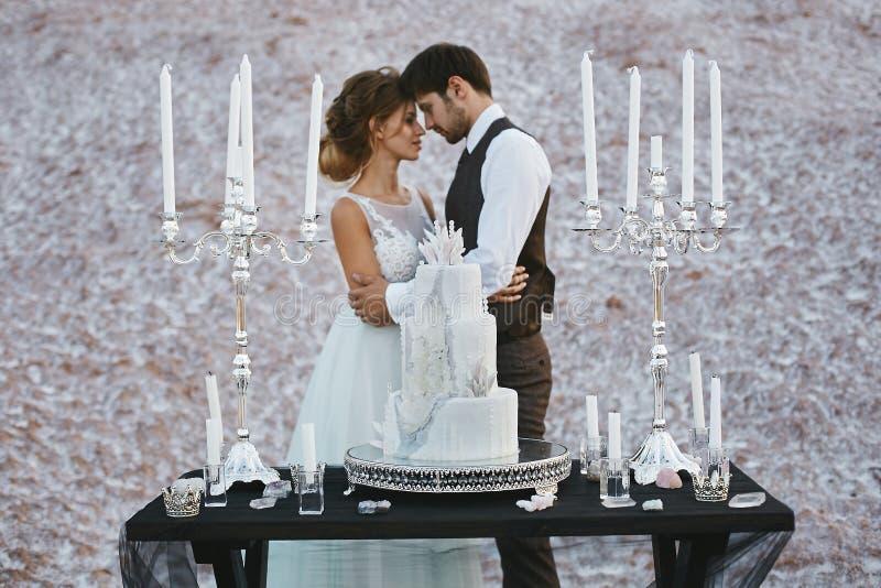 Kreatywnie i elegancki ślubny tort na drewnianym stole przed parą sympatie zdjęcia stock
