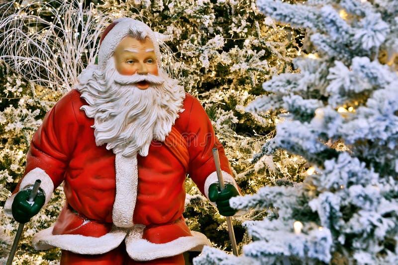 Kreatywnie kolorowa postać Święty Mikołaj z kija narciarstwem wśród śnieżnych jaskrawych drzew obraz stock