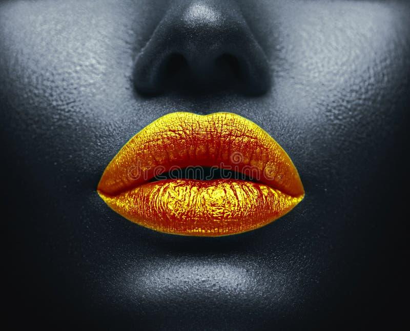 Kreatywnie kolorowy makeup Bodyart, lipgloss na seksownych wargach, dziewczyny usta Złote wargi na czarnej skórze obraz royalty free