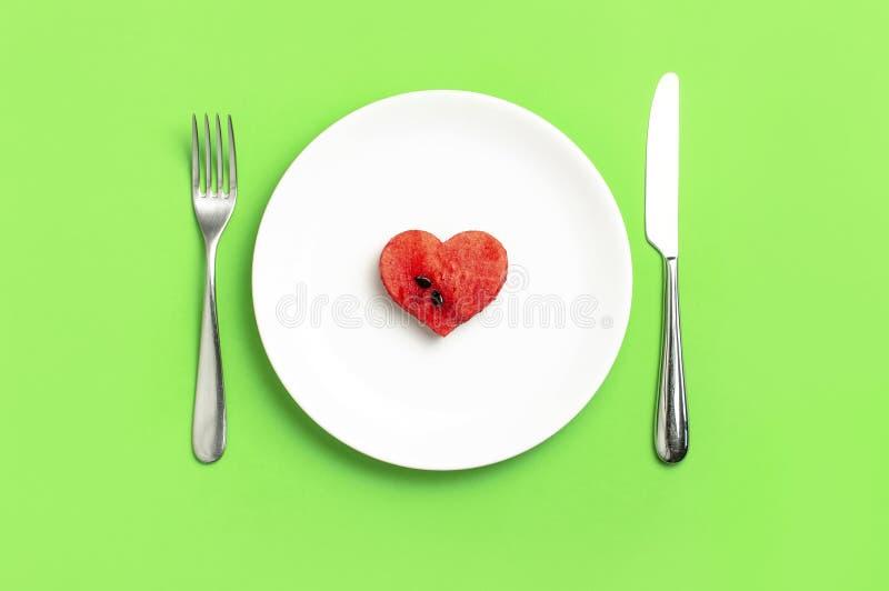 Kreatywnie lato karmowej diety pojęcie Soczyści plasterki dojrzały czerwony arbuz w formie serca w bielu talerzu, nóż, rozwidleni zdjęcia stock
