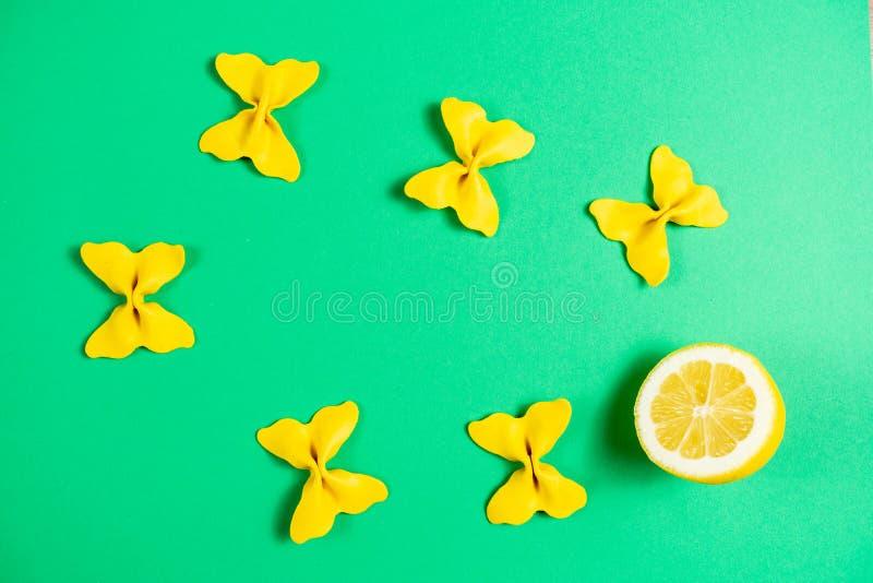 Kreatywnie lato układ robić cytryna i barwiący makaron manny papillon na jaskrawym - zielony tło Owocowy minimalny pojęcie zdjęcia stock
