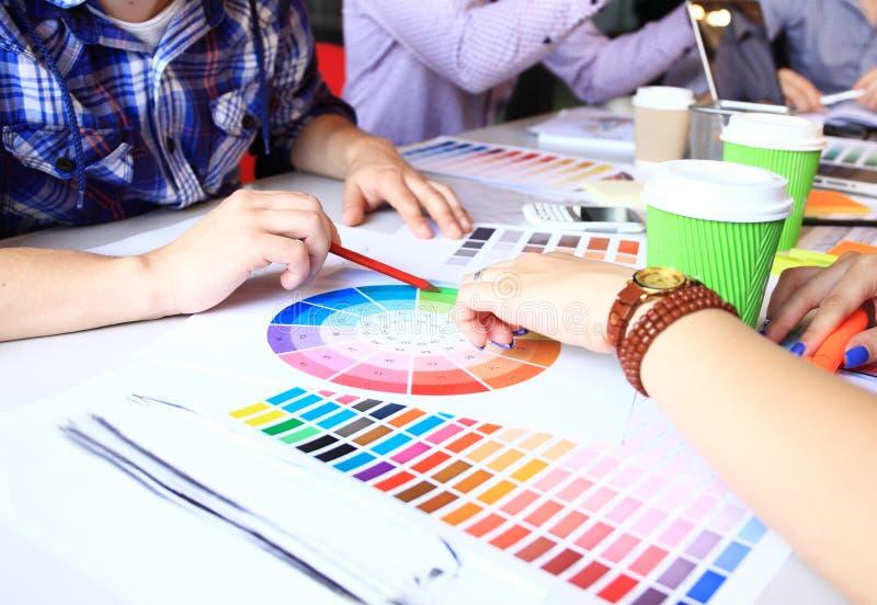 Kreatywnie ludzie miejsc pracy Zakończenie widok ręki młoda projektant kobieta pracuje z kolor paletą przy biurowym biurkiem zdjęcie stock