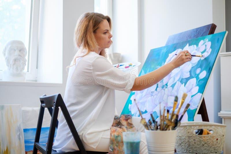 Kreatywnie malarz maluje kolorowego obrazek w jej studiu zdjęcie stock