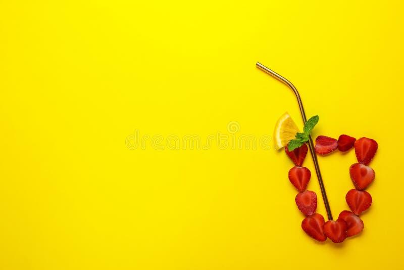 Kreatywnie mieszkania nieatutowy skład z truskawkami i cytrus pokrajać jako lato koktajl na koloru tle zdjęcie royalty free