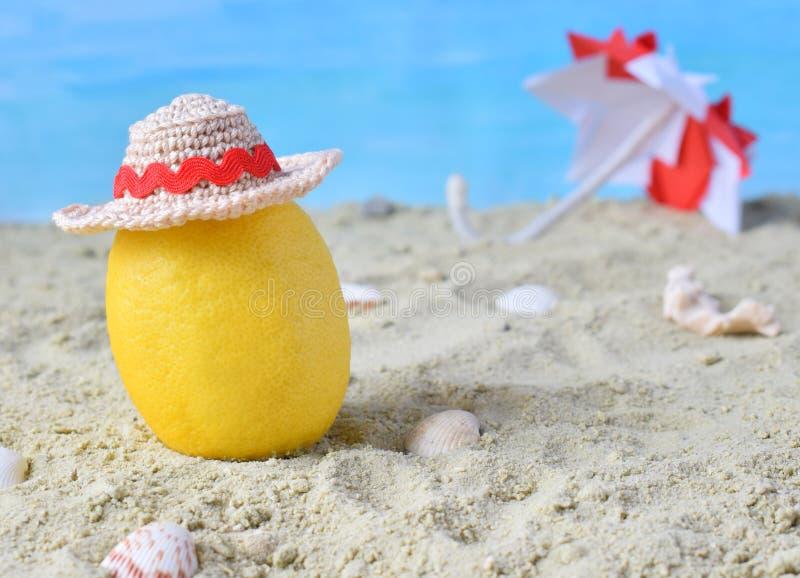 Kreatywnie minimalny lato pomysł Cytryna cytrusa modniś w bambusowym kapeluszu i plażowym parasolu na piasku Tropikalny plażowy p fotografia royalty free