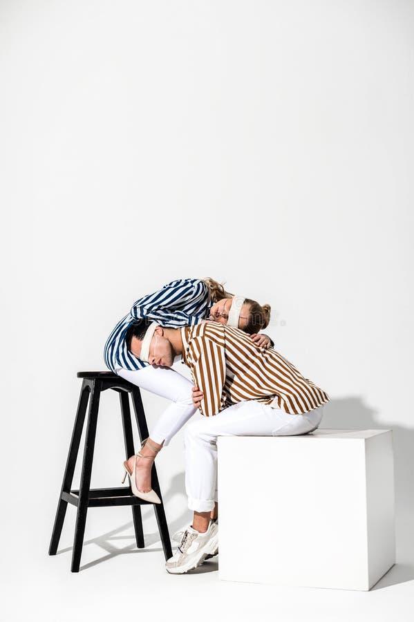 Kreatywnie modele jest ubranym pasiaste koszula opiera na each inny zdjęcie royalty free