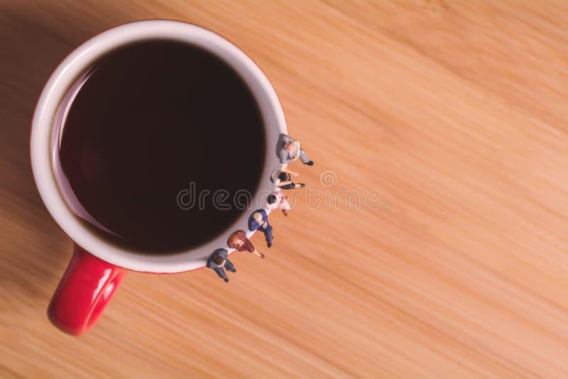 Kreatywnie pojęcie o pić kawę i czekać Miniaturowi ludzie siedzą na filiżance fotografia royalty free