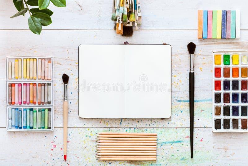 Kreatywnie pracy biurko dla wyrażenia, farb muśnięcia, paintbox z akwarelami, kredki, ołówki i notatnik, tapetujemy na bielu fotografia royalty free