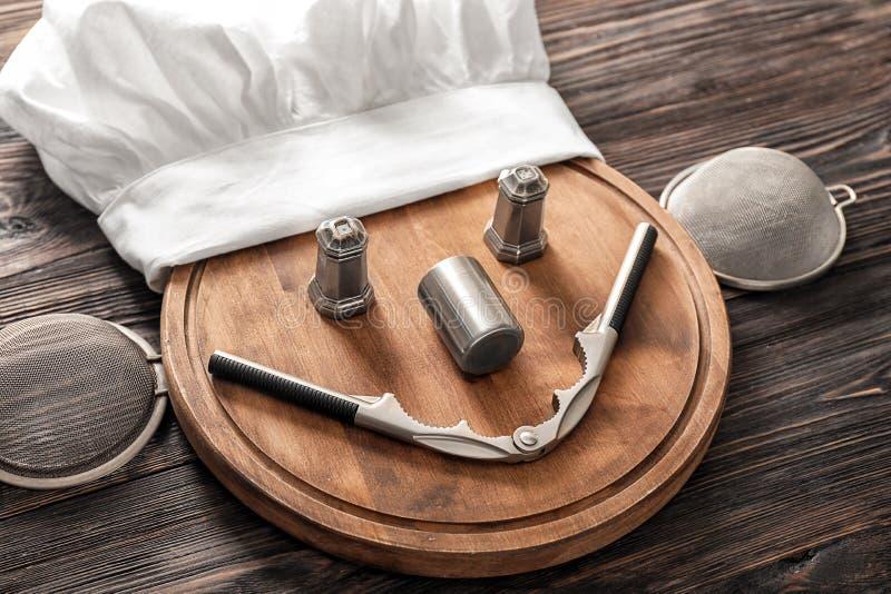 Kreatywnie skład z szefa kuchni kapeluszem, tnącą deską i kuchennymi naczyniami na drewnianym tle, obrazy royalty free