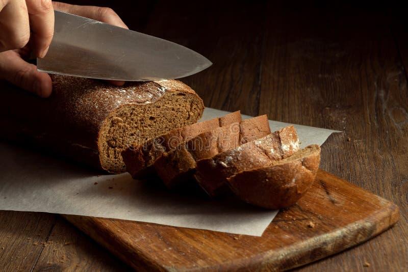 Kreatywnie tło, samiec wręcza rżniętemu żyto chlebowi w górę na drewnianej tnącej desce, mieszkanie nieatutowego, kopii przestrze obrazy stock