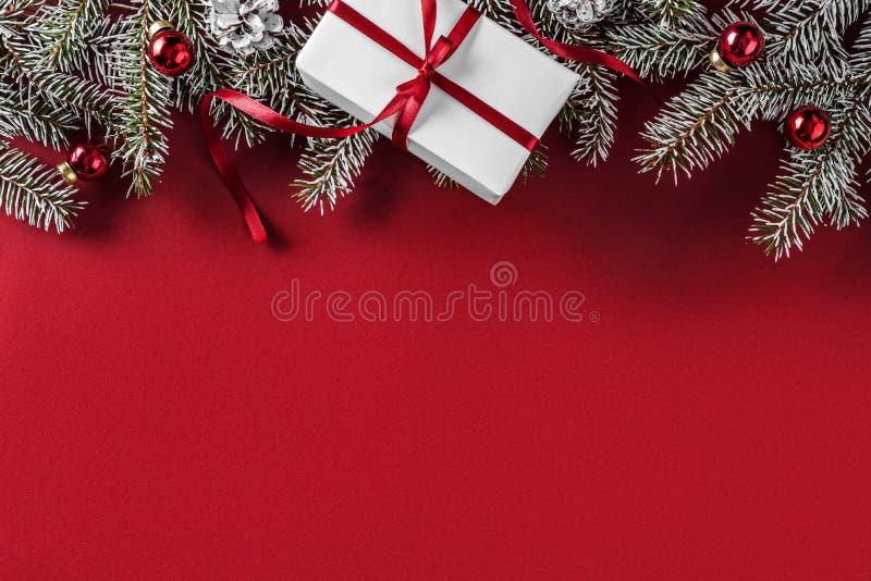 Kreatywnie układ rama robić Bożenarodzeniowa jodła rozgałęzia się, sosnowi rożki, prezenty, czerwona dekoracja na czerwonym tle fotografia royalty free