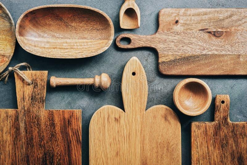 Kreatywnie układ ustawiający drewniani kuchenni naczynia, tnące deski, puchar, talerz, moździerz i tłuczek, miarka Mieszkanie nie fotografia royalty free