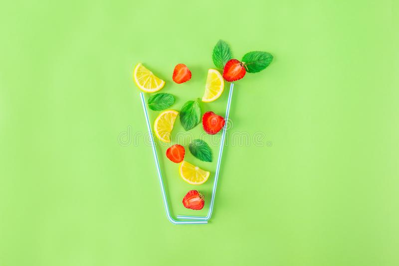 Kreatywnie układu lemoniady truskawkowi składniki - cytryna, mennica, jagody spada w szkle robić z koktajl słoma na zielonym back obrazy stock