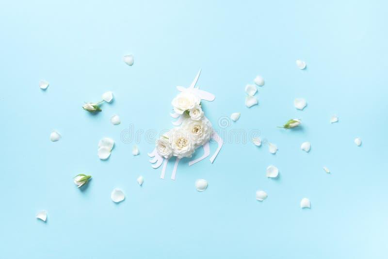 Kreatywnie uk?ad Biała jednorożec z kwiatami nad błękitnego papieru tłem Zaproszenia lub wakacje karta dla urodziny Lato fotografia royalty free