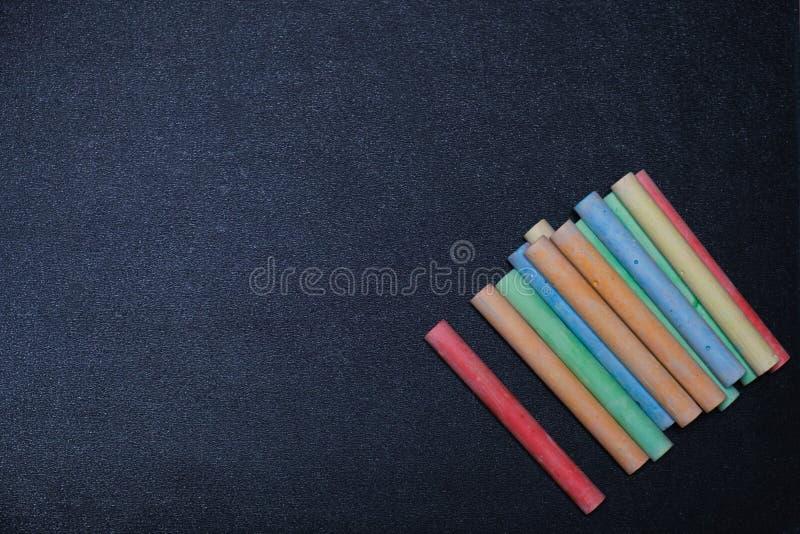 Kreda nacierająca out na blackboard dla tła Pusty pusty czarny chalkboard z kolorową kredą zdjęcie royalty free