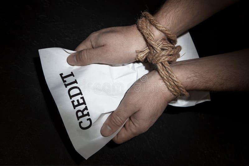 Kredietlimieten financiële kansen De mens met zijn die handen met kabel worden gebonden houdt verfrommeld blad met het inschrijvi stock foto's