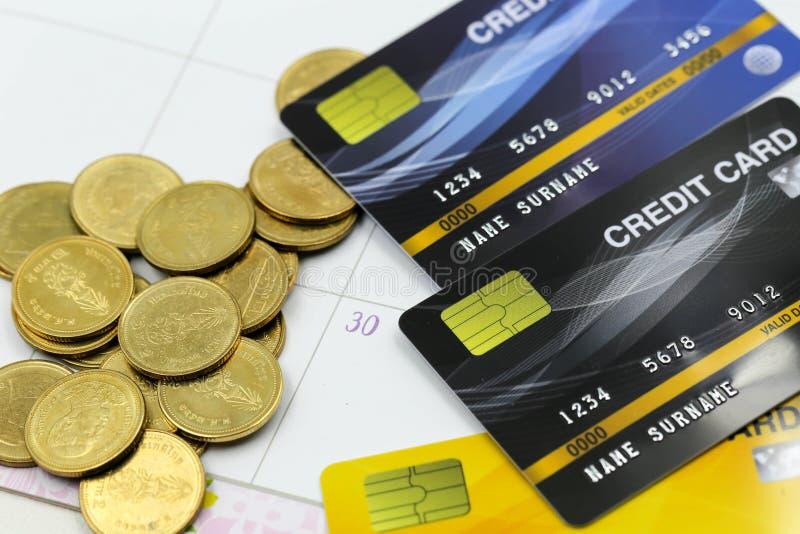 Kreditkarte mit Stapeln des goldenen Scheinhintergrundes der Münzen Feder, Brillen und Diagramme lizenzfreie stockbilder