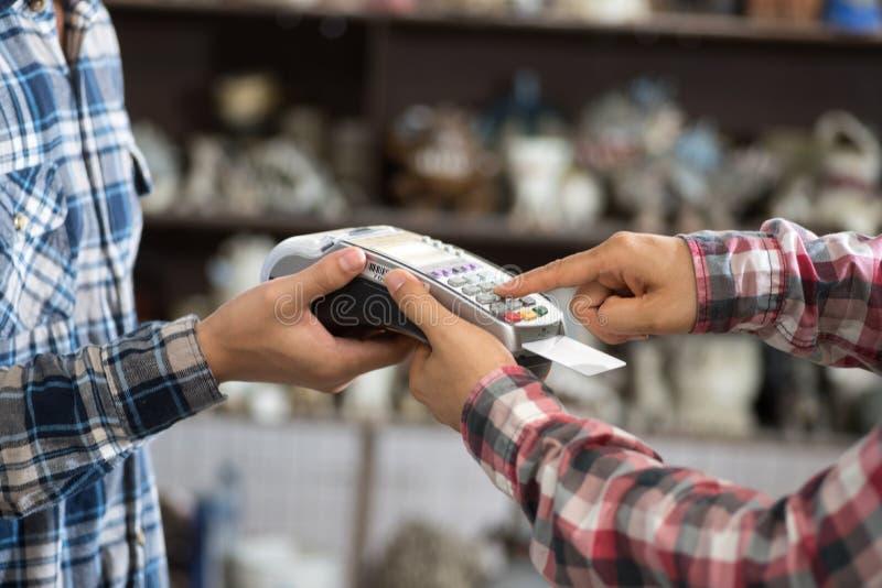 Kreditkartemaschine, die durch Mannhände hält lizenzfreie stockfotografie