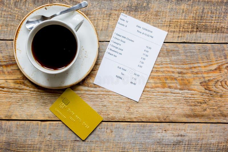 Kreditkort för att betala, kaffe och kontroll på åtlöje för bästa sikt för kaféträskrivbordbakgrund upp royaltyfri bild