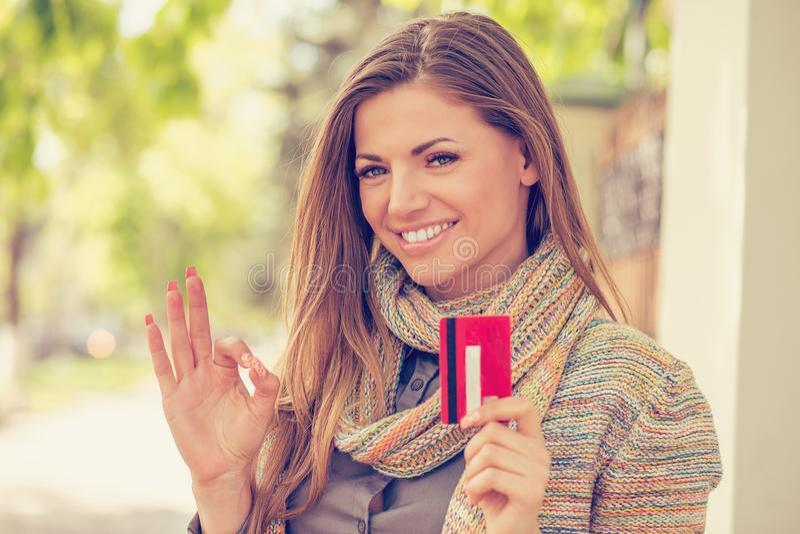Kreditkort för visning för Toothy leendekvinna hållande utomhus på en stadsgatabakgrund royaltyfri bild
