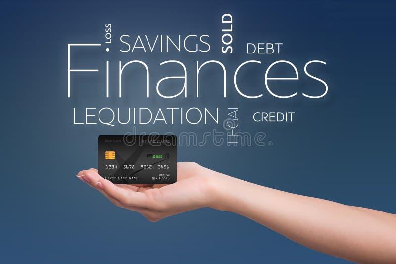Kreditkort i en kvinnlig hand på blått arkivfoto