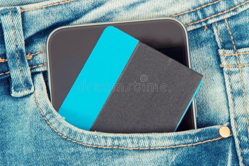 Kreditkort och mobiltelefon för cashless betala i fack av jeans packa ihop finans royaltyfria bilder