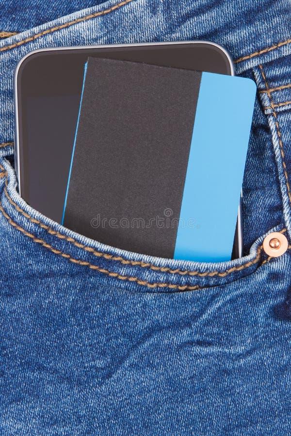 Kreditkort och mobiltelefon för cashless betala i fack av jeans packa ihop finans arkivbild
