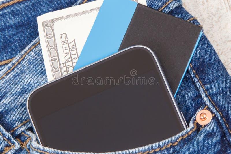 Kreditkort, valutor dollar och mobiltelefon för cashless betala i fack av jeans packa ihop finans arkivbild
