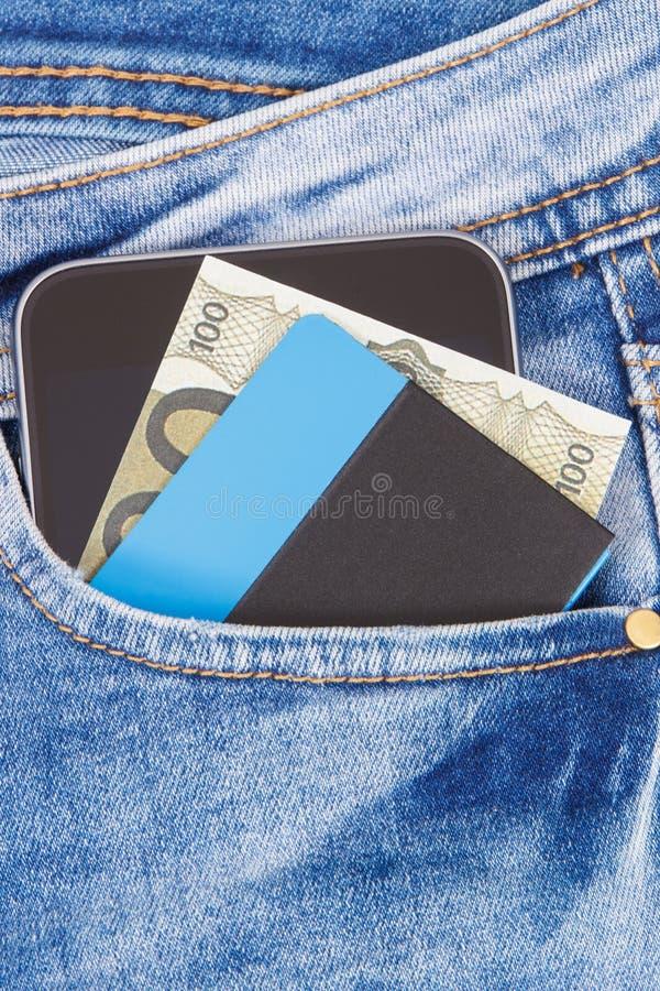 Kreditkort, valutor euro och mobiltelefon för cashless betala i fack av jeans packa ihop finans arkivfoto