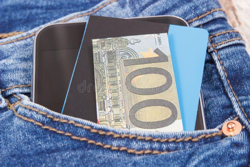 Kreditkort, valutor euro och mobiltelefon för cashless betala i fack av jeans packa ihop finans arkivbilder