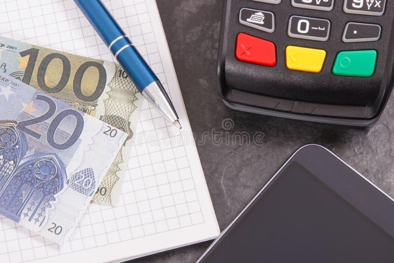Kreditkortavläsare, mobiltelefon med NFC-teknologi för cashless betalningtransaktion, notepad för anmärkningar och euro Aff?r arkivbilder