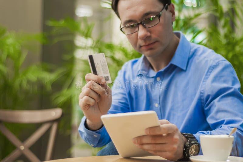 Kreditkorten för handen för man` s tonar den hållande med minnestavlan för att shoppa online-begrepp, den selektiva fokusen och t royaltyfri foto