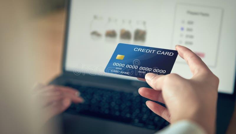 Kreditkorten för kvinnahandinnehavet och pressbärbar datordatoren skriver in betalningkoden för produkten Betala direktanslutet f arkivbilder