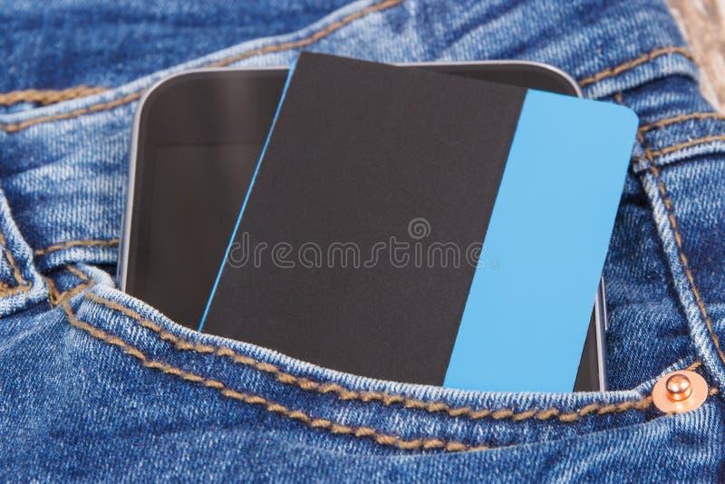 Kreditkorten med mobiltelefonen i jeans stoppa i fickan Cashless betala f?r att shoppa begrepp royaltyfri bild