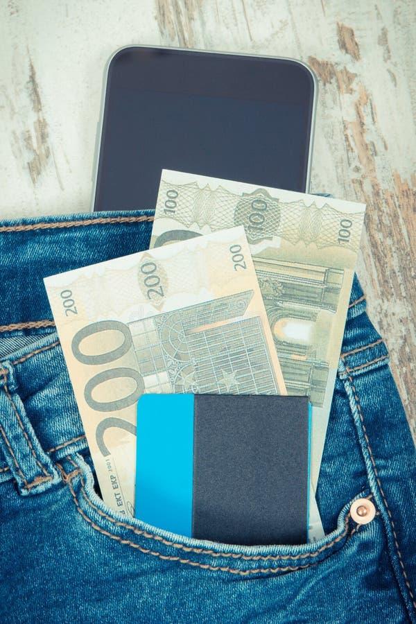 Kreditkorten valutaeuro i jeans stoppa i fickan och smartphonen Cashless eller kontantbetalningbegrepp royaltyfri foto