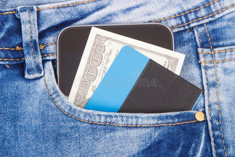 Kreditkorten, valutor dollar och smartphonen i jeans stoppa i fickan Cashless eller kontantbetalningbegrepp arkivfoton