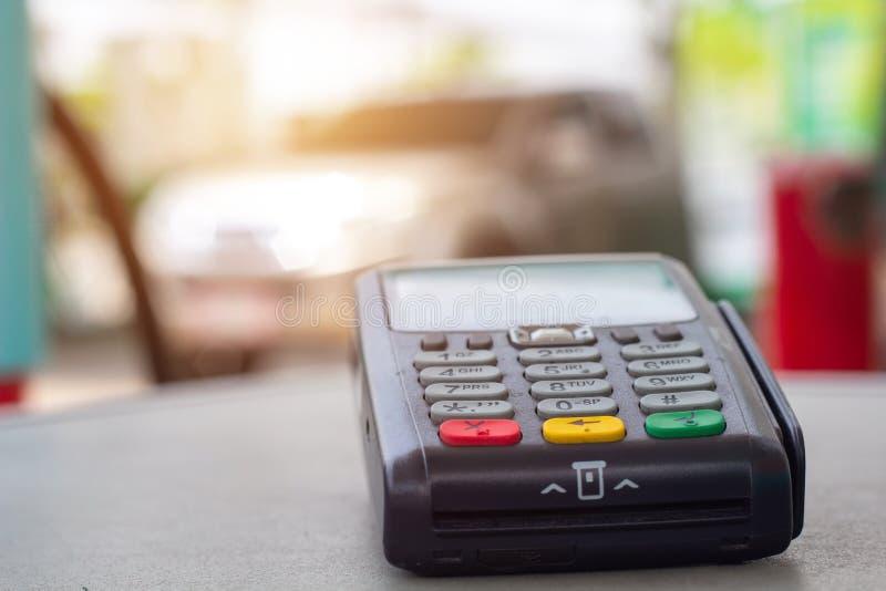 Kreditkortmaskin med bilen som tankar bensin på bensinstationen i bakgrund arkivfoton