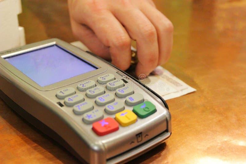 Kreditkortmaskinen och en mans hand sätter kassa royaltyfri fotografi