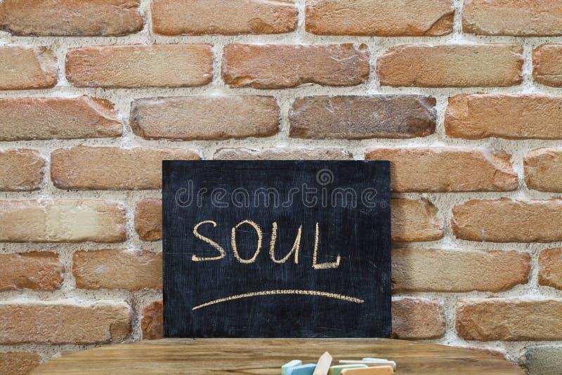 Kredowa deska z słowem dusza tonie ręcznie i pisze kredą na drewnianym stole na ściany z cegieł tle zdjęcie stock