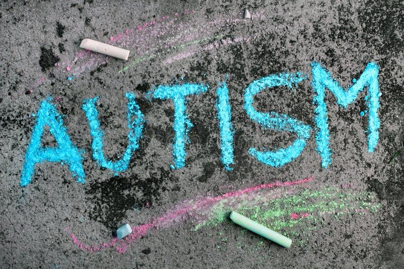 Kredowy rysunek: błękitny słowo autyzm i kawałki kreda fotografia royalty free