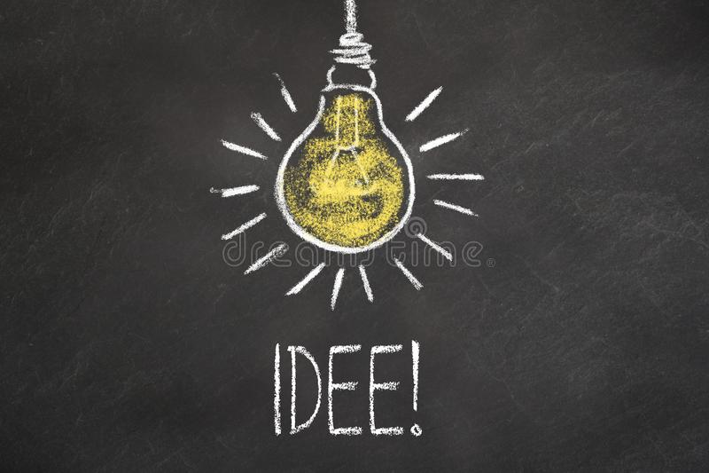 Kredowy tekst i lightbulb na chalkboard ?Idea ? Przek?ad: ?pomys? ? ilustracja wektor