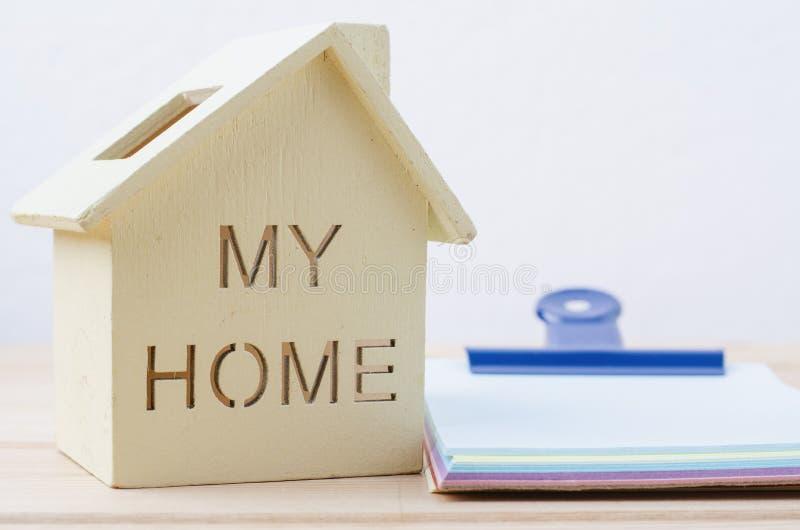 Kredyta mieszkaniowego i inwestycj pojęcie drewniany dom i notepad na d, zdjęcia royalty free