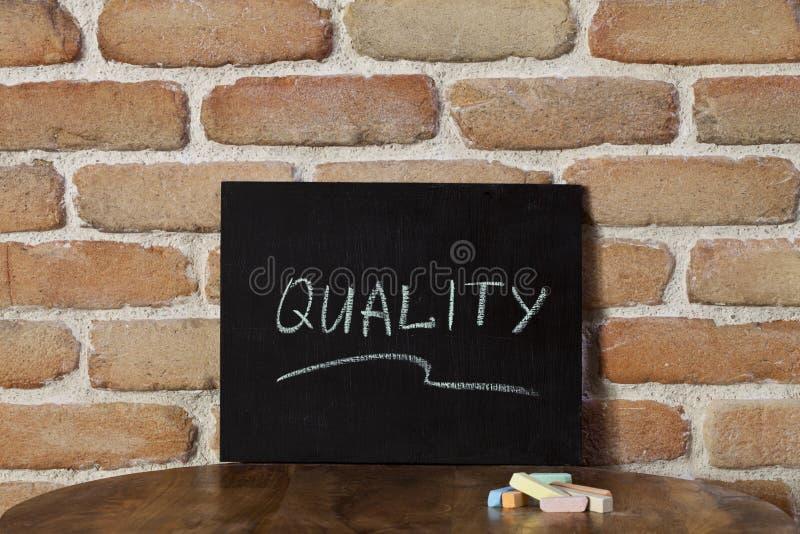Kreidebrett mit dem Wort QUALITÄT auf Holztisch auf Backsteinmauerhintergrund eigenhändig ertrinken lizenzfreies stockbild