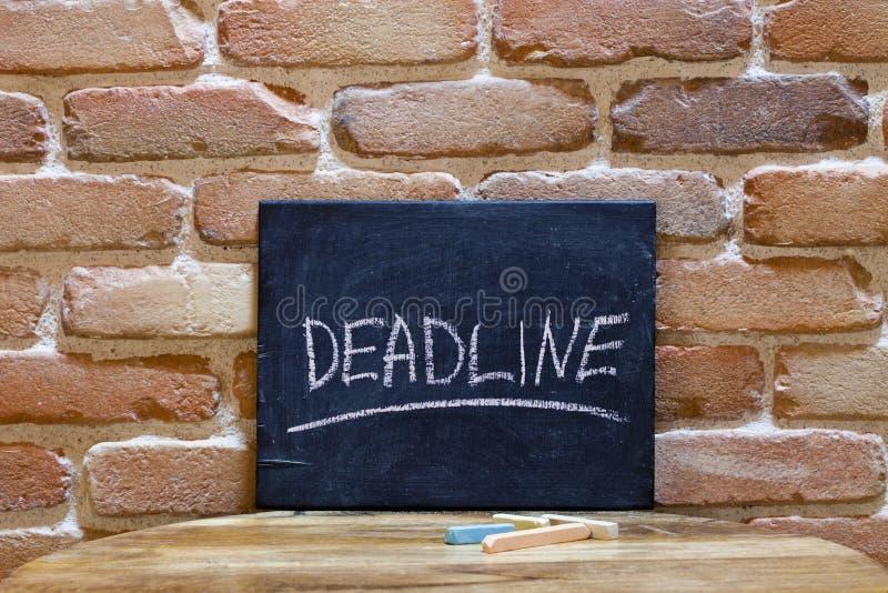 Kreidebrett mit der Wort Frist ertrinken eigenhändig auf Holztisch auf Backsteinmauerhintergrund lizenzfreie stockfotografie