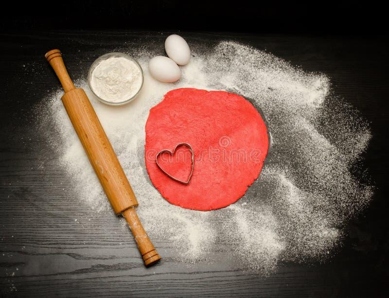 Kreis des roten Teigs mit Herzformausschnitt Schwarze Tabelle besprüht mit Mehl, Nudelholz und Eiern lizenzfreie stockbilder