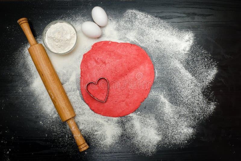 Kreis des roten Teigs mit Herzformausschnitt Schwarzes Tabelle sprink stockfoto