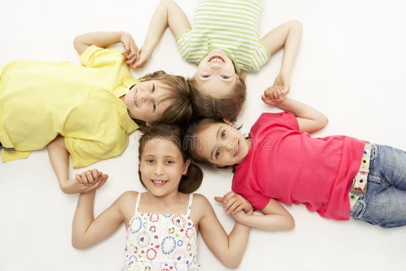 Kreis von vier jungen Freunden, die h lächeln und anhalten lizenzfreie stockfotos