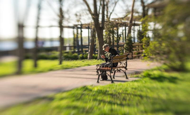 Lonely elderly man sits on a bench in a colorful spring park. Kremechuk, Poltava region / Ukraine - April 20 2018: elderly single man is sitting on a garden royalty free stock photos