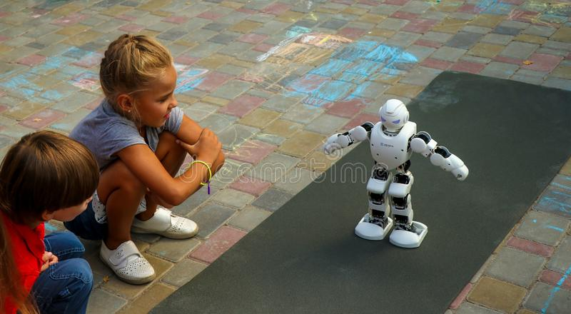 Kremenchuk, Ukraine - 3.08.2019: Demonstration of high technology of the future, The Smart UBTECH Humanoid Robot surrounded by. Children, horizontal orientation royalty free stock photos